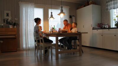 Familjen Forsblom dricker te vid köksbordet.