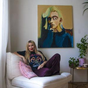 Meikkitaiteilija Piia Hiltunen istuu valkoisessa nojatuolissa. Takana seinällä on iso maalattu naisen muotokuva.