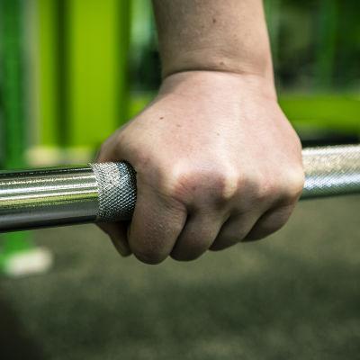 Käsi painonnostotangolla.