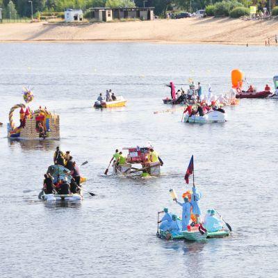 Människor deltar i ett flottrace med flottar gjorda av mjölkburkar i Jelgava, Litauen.