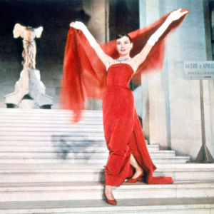 Audrey Hepburn punaisessa iltapuvussa Louvren portailla. Kuva elokuvasta Rakastunut Pariisissa.