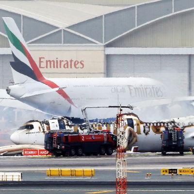 Flygplanet ligger på landningsbanan med övre delen av plankroppen sönderbränd.