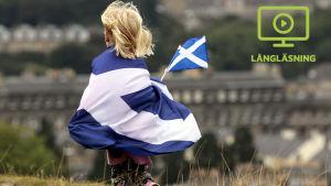 Ett barn tittar över Edinburgh invirat i Skottlands blå-vita flagga och med Skottlands flagga i handen.