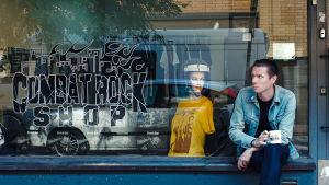 Mies istuu kivijalkakaupan ikkunan edessä