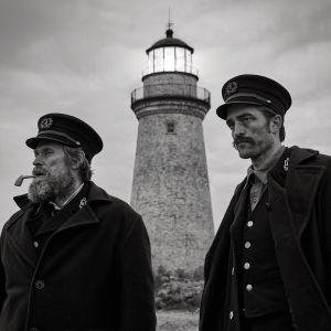En svartvit bild på Thomas Wake (Willem Dafoe) och Ephraim Winslow (Robert Pattison) står nedanför en fyr och tittar ut mot havet.