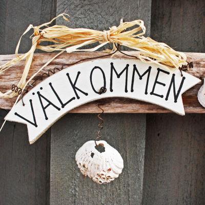 En skylt på en dör med texten välkommen. Skylten ser ut att vara gjord av drivved och den är dekorerad med snäckskal.