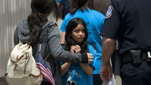 En flicka tittar skrämd upp mot en gränspolis.
