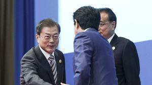 Två män skakar hand med varandra. Shinzo Abe ser på Moon Jae-in.
