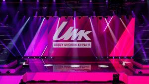"""UMK20-finaalin lavakuva, screenillä UMK-grafiikoilla teksti """"Uuden musiikin kilpailu"""", kuvassa myös katsomoa."""
