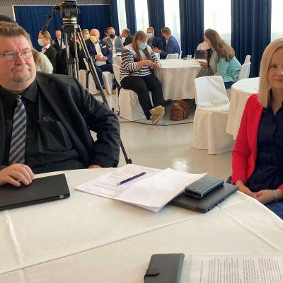 Kolme ihmistä ravintolapöydän ääressä. Taustalla muita ihmisiä istumassa omissa pöydissään perussuomalaisten eduskuntaryhmän kesäkokouksessa Torniossa.