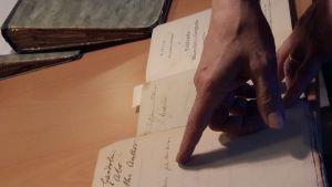 en hand pekar mot något i en gammal boks första blad