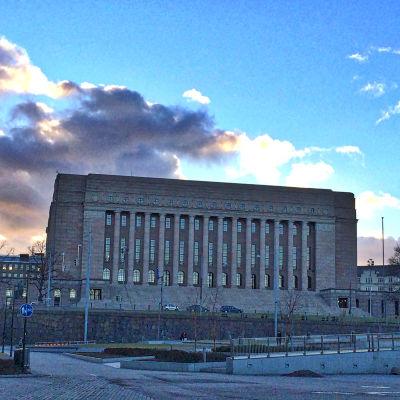 Riksdagshuset i Helsingfors fotat rakt framifrån i kvällsljus.