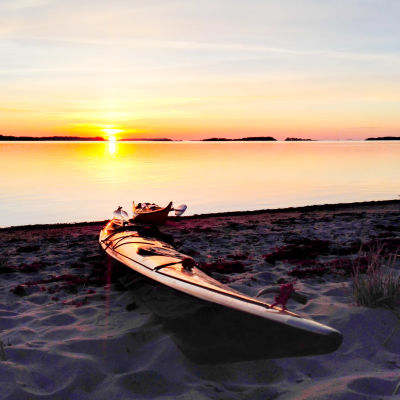 Två kajaker är uppdragna på en sandstrand, som badar i ljuset av de sista solstrålarna där solen går ner över havet.