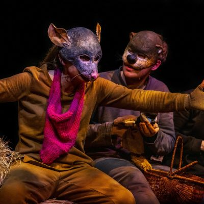 Tre skådespelare i djurmasker sitter på en höbal.
