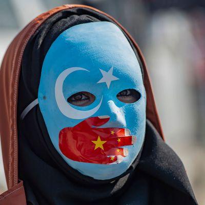 En maskförsedd demonstrant visar sitt stöd för uigurerna under en protestaktion utanför Kinas konsulat i Istanbul
