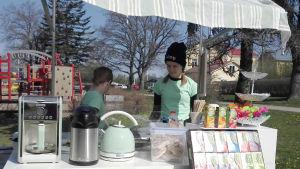 Två flickor står bakom en vagn som fungerar som pop-up restaurang.