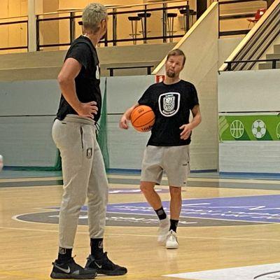 Mustapaitainen korisvalmentaja Pieti Poikola neuvoo harjoituksissa pelaajaa, valmentajalla kainalossaan koripallo. Pelaaja kuuntelee seisten kädet lanteillaan.