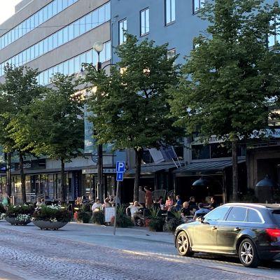 Keskustan katu, auto ajaa katua, tien varrella kerrostaloja ja ravintolan terassilla ihmisiä