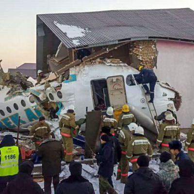 En bild från Kazakstans räddningsmyndigheter visar räddningsarbetare runt flygplansvraket, vars nos kraschat in i ett tvåvåningshus.