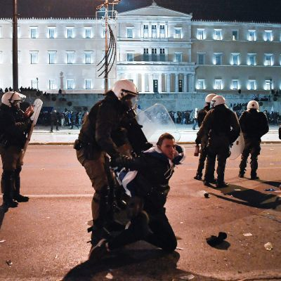 Grekisk kravallpolis grep demonstranter utanför parlamentet i Aten natten till fredagen.