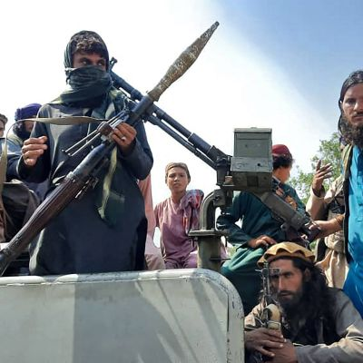 Talibaner med vapen sitter på ett fordon.
