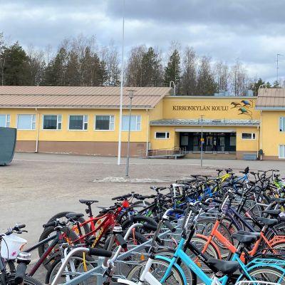 Keltainen koulurakennus ja tyhjä piha jossa pyöriä parkissa