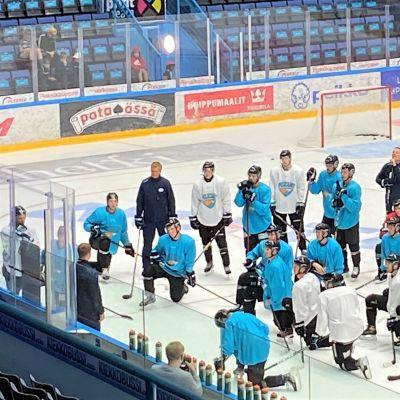 Jääkiekkokaukalon jäällä pelaajat polviasennossa ryhmässä katsovat kun mies neuvoo