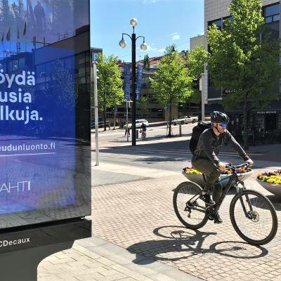 Mies polkupyöräilee Lahden keskustassa 2020.