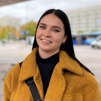 Lahtelainen Roosa Niemi katsoo kameraan ja hymyilee matkakeskuksen kaukobussien lähtölaiturilla