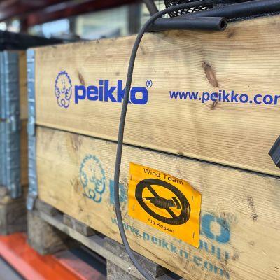 Peikon tehdassalista kuva laatikosta jossa Peikon logo