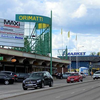 autot ajavat kadulla, jonka varrella kauppoja