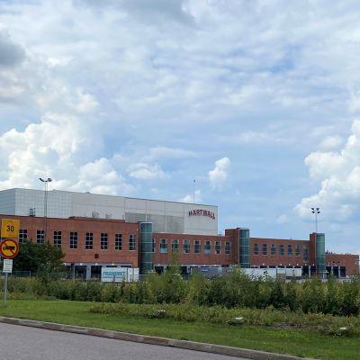 punatiilinen iso tehdasrakennus aitauksen takana, rekka-autoja pihassa