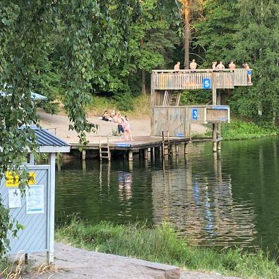 Järven uimaranta, puinen hyppytorni, jossa ihmiset hyppäämässä veteen