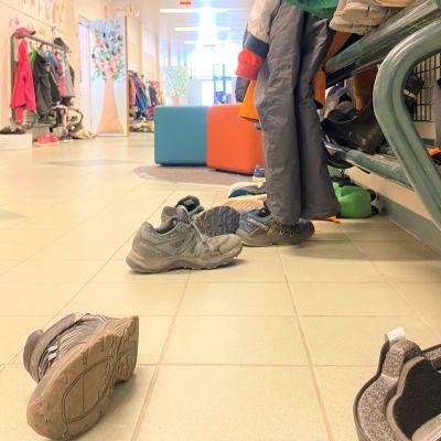 Koulun käytävä, lattialla kenkiä, naulakossa vaatteita