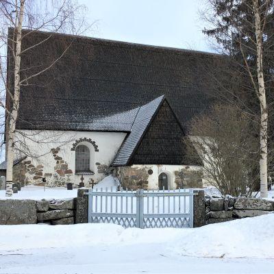 Isonkyrön vanha kirkko talvimaisemassa kuvattuna muurin ulkopuolelta.