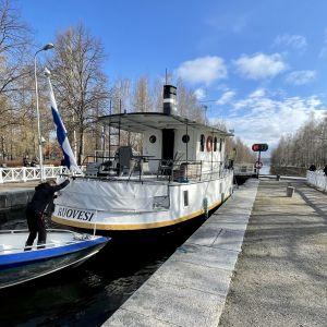 Vene ja pieni laiva odottavat sulun avautumista kanavassa.