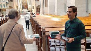 Fayyah Alessa, en man med glasögon och grön skjorta, ger en psalmbok till en kyrkobesökare inför högmässan i Åbo Domkyrka.