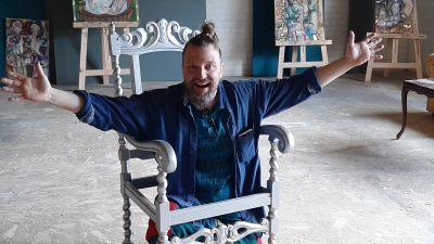 konstnären Mikki Paajanen spexar innanför en snidas stol som målats i silver