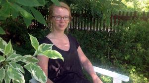Maria Turtschaninoff sitter i en stol i en lummig trädgård.