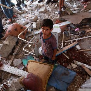 Ett barn mitt i ruinerna i FN-skola som träffades av israeliska granater i Jabalya i Gaza.
