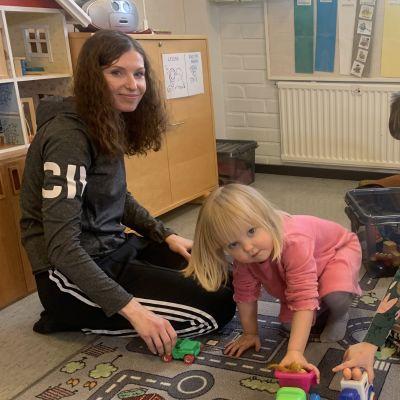En ung kvinna med långt hår sitter på knä och leker med tre dagisbarn.