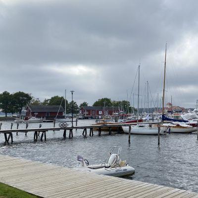Båtar ligger förtöjda vid en brygga i en småbåtshamn.