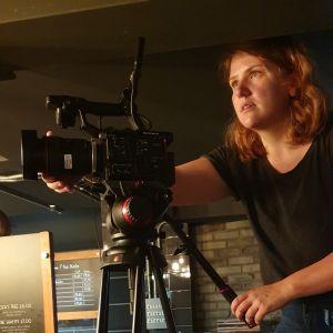 Frida Johansson filmar med en filmkamera.