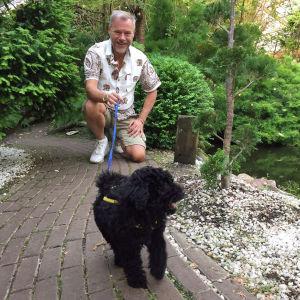Mies ja musta pikkukoira japanilaisessa puutarhassa