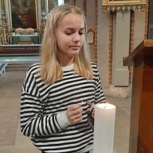 Cecilia Mäki-Kuutti, en flicka med långt ljust hår och en svartvitrandig skjorta, tänder ett ljus i Åbo domkyrka.