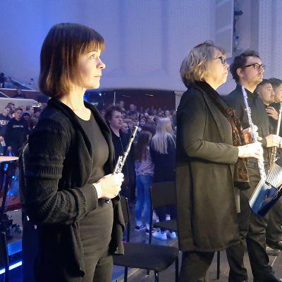 Anu Honkanen, en dam med svart tröja, håller i sin piccolafjöjt inför en konsert i Åbo konserthus.