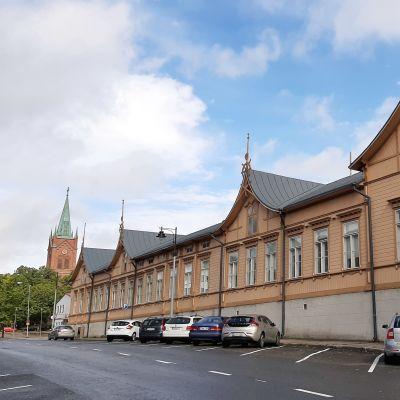 Nystads nya kyrka med högt, spetsigt torn och ett långt gulbrunt hus, där Nystads bibliotek finns.