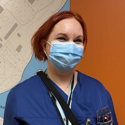 Sairaalan henkilökuntaan kuuluva nainen hymyilee kameralle
