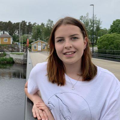 En ung kvinna med långt hår står på en bro över en älv med gula hus i bakgrunden