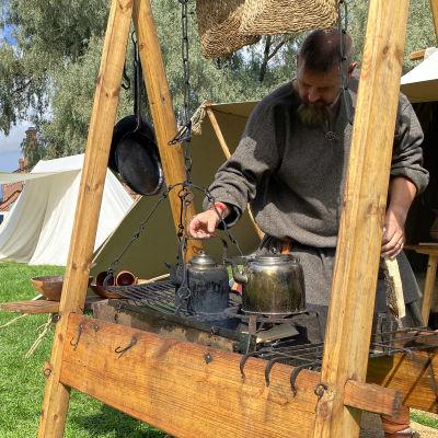 Historianelävöittäjä viikinkiteltan edessä keittopaikalla.